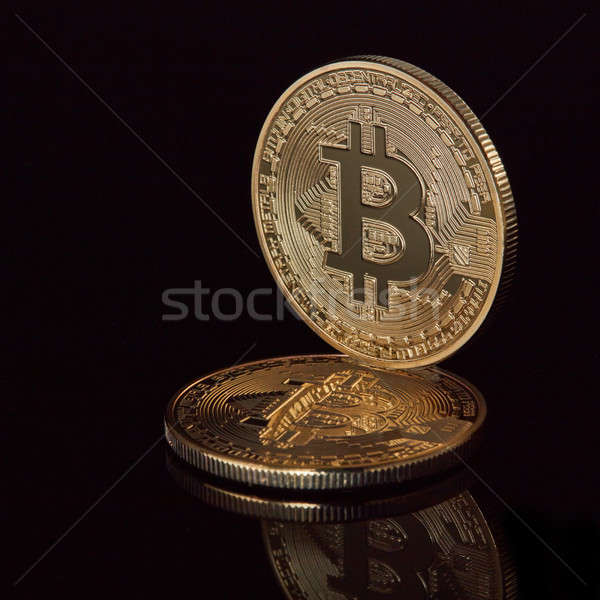 New virtual money stacked crypto currency golden bitcoins coins on black reflective surface backgrou Stock photo © artjazz
