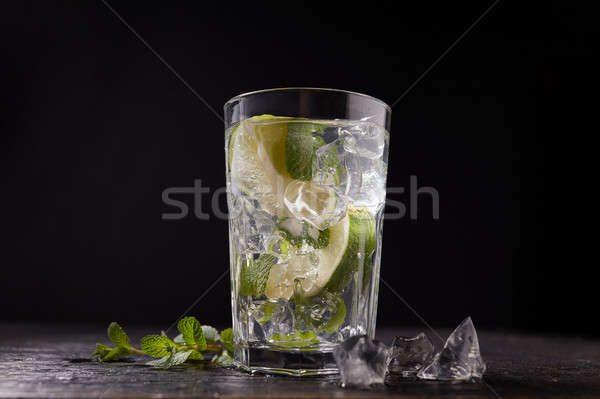 Cocktail with fresh fruit lime, mint and ice in a glass on dark Stock photo © artjazz