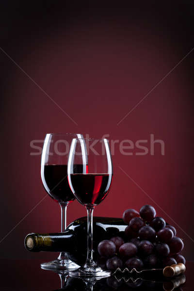 Wine in glasses with grape and bottle on red Stock photo © artjazz