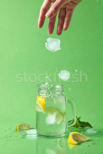 A woman's hand throws a piece of ice into a glass jar with a natural lemonade. Ice cubes fall into a Stock photo © artjazz