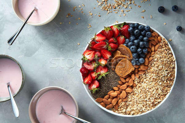 Stock photo: yogurt in glasses with granola, berries and chia seeds for healthy breakfast on a concrete backgroun