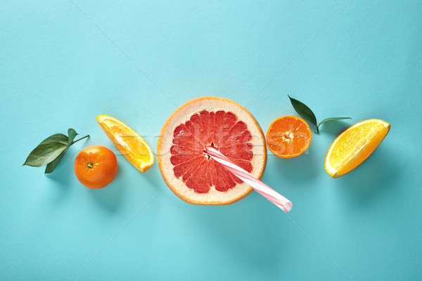 Orange slices and a half of grapefruit with a straw on a blue background in the form of a pattern Stock photo © artjazz