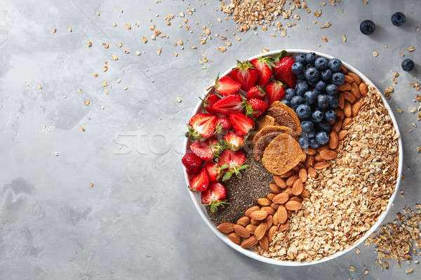 Fresh berries, almonds, oatmeal and granola in a plate with gray concrete background top view. Healt Stock photo © artjazz