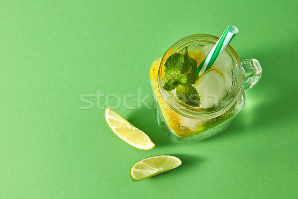 Refreshing homemade sparkling lemonade with ice in mason jar, slices of lime and lemon, leaf of mint Stock photo © artjazz