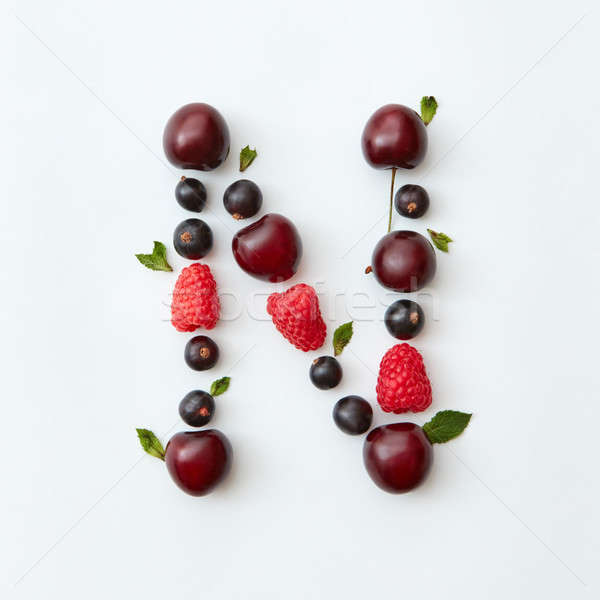 Fruits pattern of letter N english alphabet from natural ripe berries - black currant, cherries, ras Stock photo © artjazz