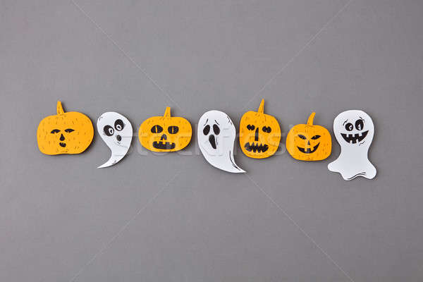 Halloween pattern from handmade paper scary ghosts and spirits, yellow pumpkins on a gray paper. Stock photo © artjazz