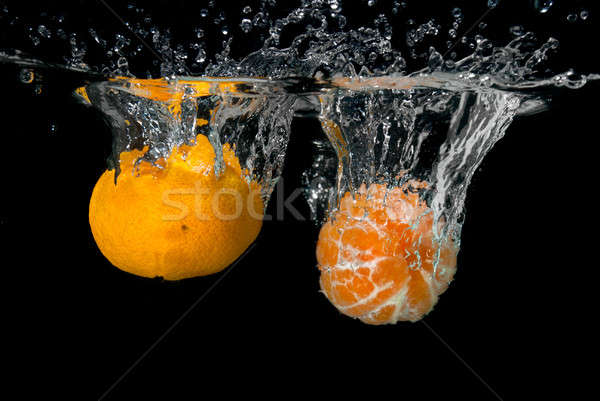 Fresh tangerines dropped into water with bubbles on black Stock photo © artjazz