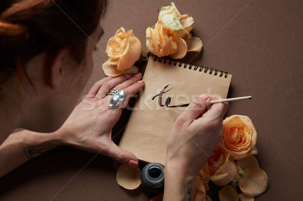 Writing a love letter with roses Stock photo © artjazz