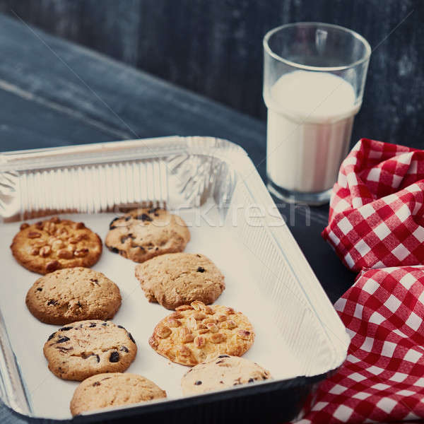 Homemade oatmeal biscuits on a baking sheet with glass of milk for Santa Claus on a black wooden tab Stock photo © artjazz