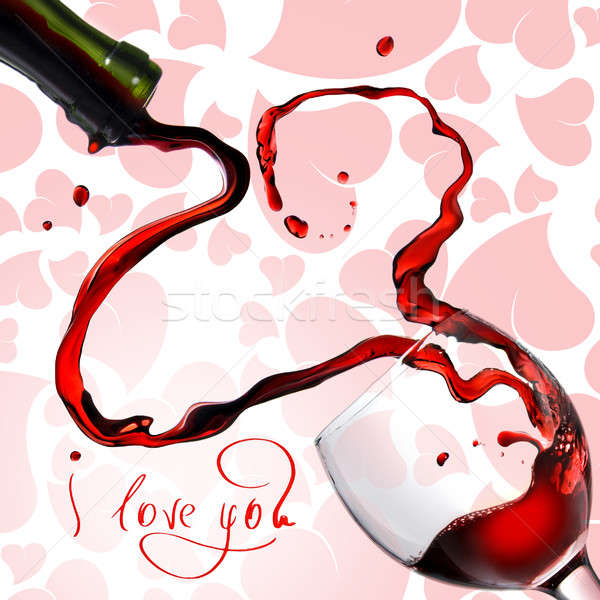 Stock photo: Heart from pouring red wine in goblet isolated on white