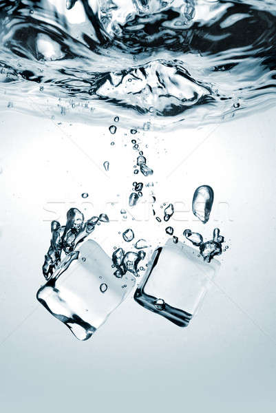 Stock photo: ice cubes dropped into water with splash