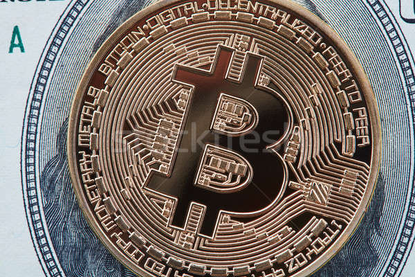 Close-up of gold Bitcoin on hundred dollars bills Stock photo © artjazz
