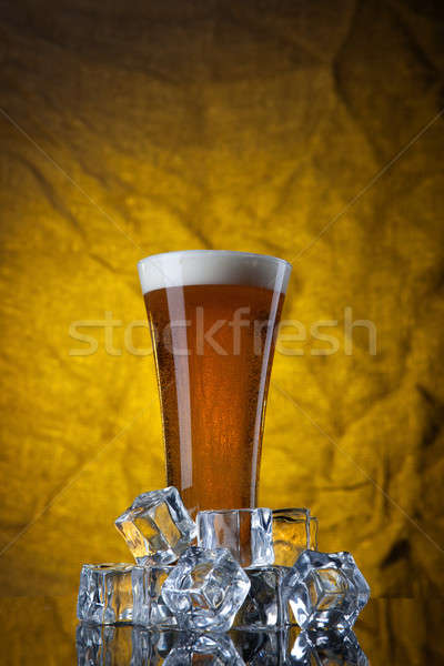 Beer in glass with ice cubes on yellow background Stock photo © artjazz