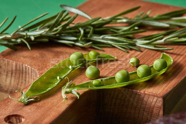 Close-up green organic clean vegetables - rosemary, pods of peas beans on a cutting wooden board on  Stock photo © artjazz