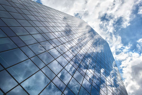 Skyscraper with reflection of blue sky and clouds Stock photo © artjazz