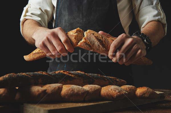 Male hands break the baguette Stock photo © artjazz