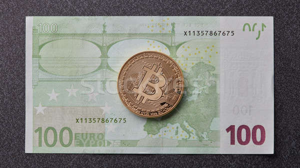 Gold bitcoin on one hundred euro banknote on a dark background Stock photo © artjazz