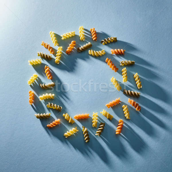 Frame in the form of a circle of multi-colored pasta on a blue background. Flat lay. Stock photo © artjazz