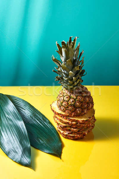 Composition of green leaves and sliced pineapple on a blue-yellow paper background Stock photo © artjazz