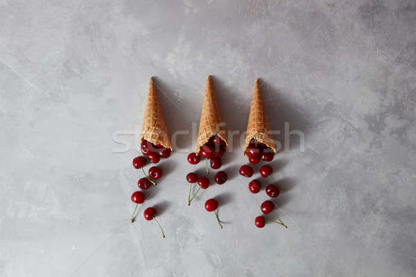 Natural organic fruits pattern on a red cherries in a waffle cup Stock photo © artjazz