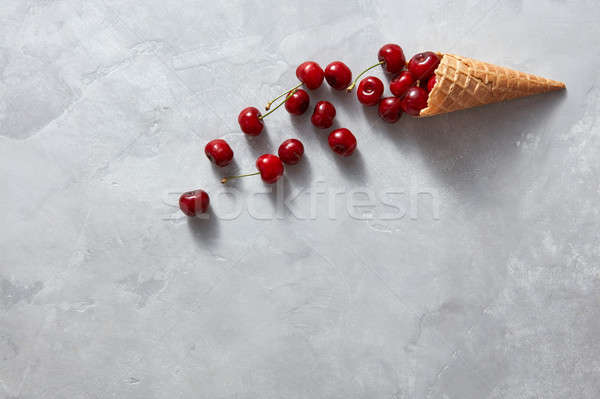 Freshly picked ripe cherries in a wafer horn on a gray table. To Stock photo © artjazz