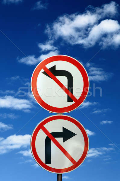 Stock photo: two opposite road signs against blue sky and clouds