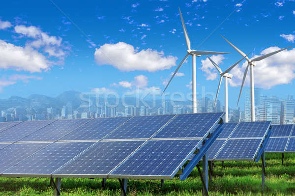 Stock photo: Solar panels and wind turbines with city