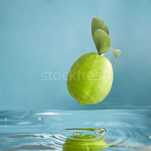 Beautiful green limes falls into water Stock photo © artjazz