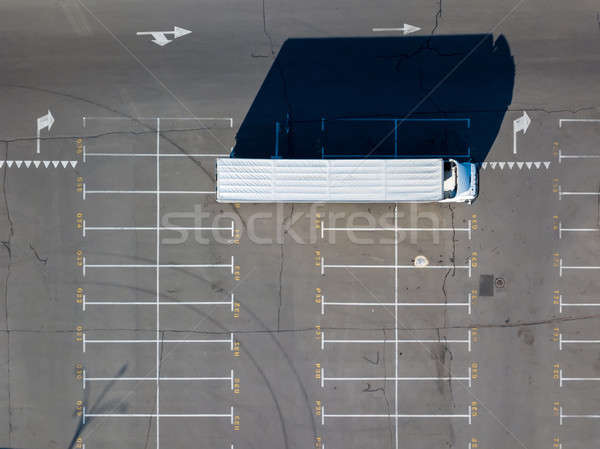 Long shadows from truck on a parking lot for cars with numbered seats in a sunny day. Stock photo © artjazz
