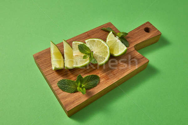 Slices of fresh green lime and sprig of green mint on a wooden brown board on a green. Ingredient fo Stock photo © artjazz