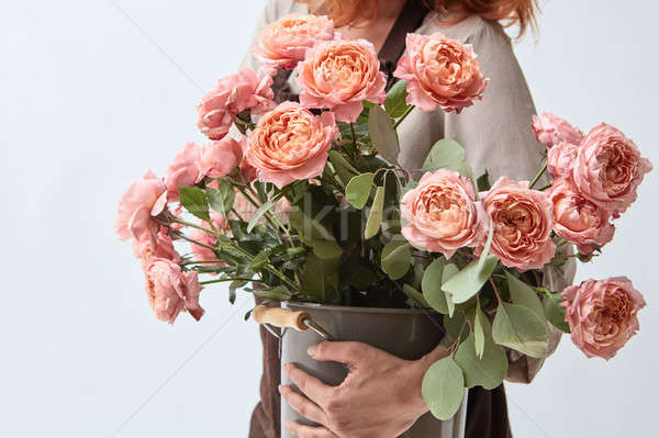 girl holding a vase with a bouquet of roses Stock photo © artjazz