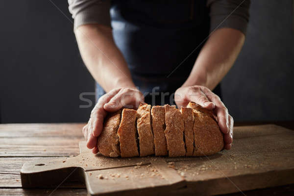 Fresh home slice bread in male's hands on the wooden board. Stock photo © artjazz