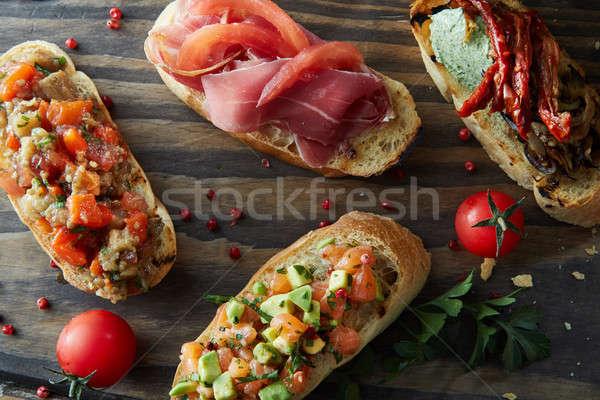 Stock photo: Italian bruschetta with roasted tomatoes, avocado, salmon, ham, peppers, herb