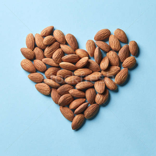 Pattern in the form of heart from almonds on a blue paper background Stock photo © artjazz