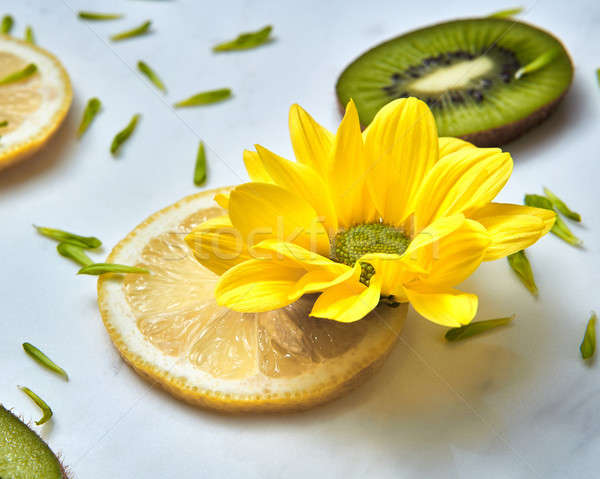 Close-up summer yellow flower, slices of kiwi, lemons and green flower petals. Stock photo © artjazz