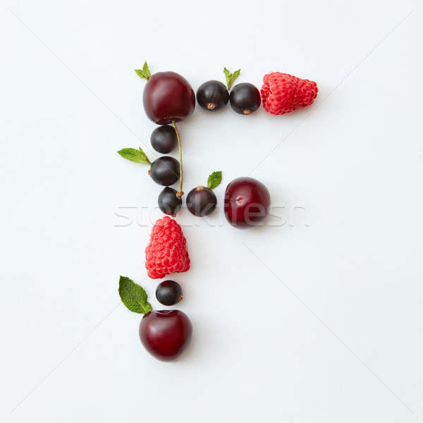 Fruits pattern of letter F english alphabet from natural ripe berries - black currant, cherries, ras Stock photo © artjazz