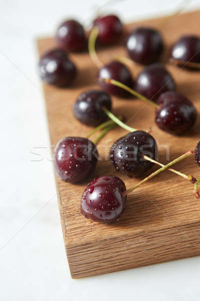 Close-up ripe sweet cherry in water droplets on a wooden board on white background with soft focus. Stock photo © artjazz