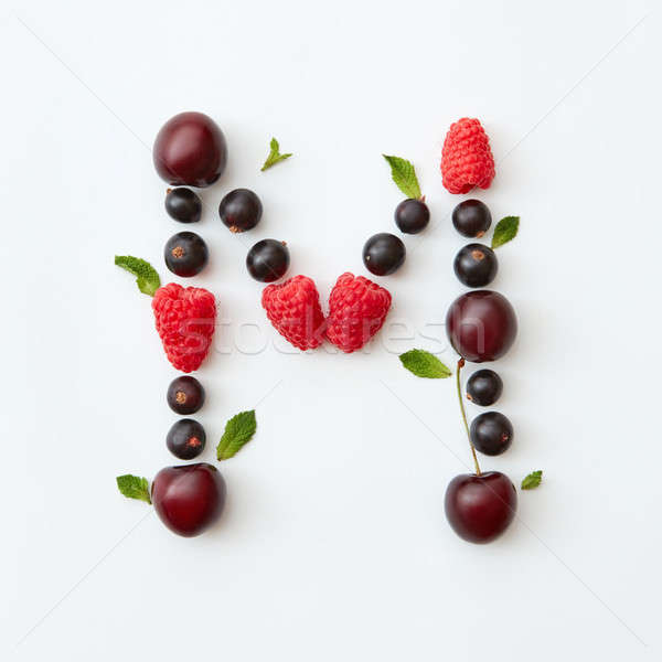 Colorful pattern of letter M english alphabet from natural ripe berries - black currant, cherries, r Stock photo © artjazz