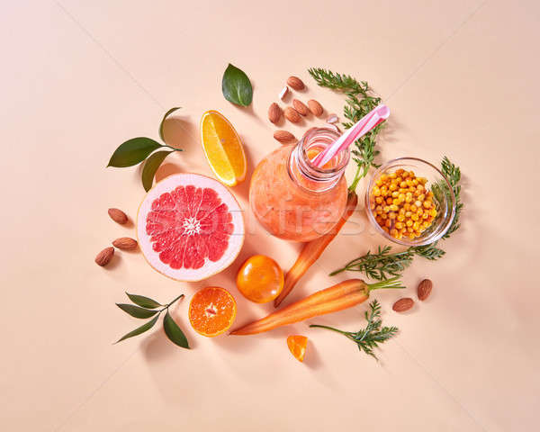 Orange smoothies from orange vegetables and fruits in a glass bottle with orange, grapefruit, carrot Stock photo © artjazz