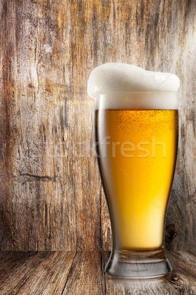 Glass of beer on wooden background Stock photo © artjazz