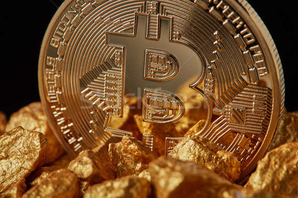 Closeup of gold nugget and Gold Bitcoin Coin on black background. Stock photo © artjazz