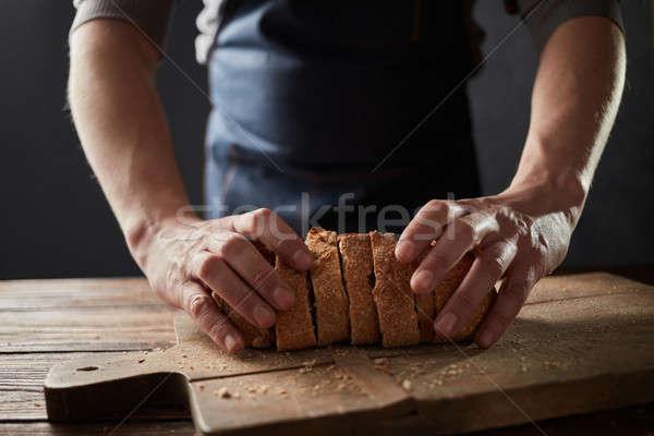 Baker man holding a healthy slice bread on a wooden board Stock photo © artjazz