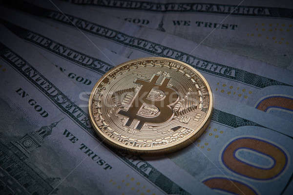 Golden bitcoin Cryptocurrency coin on a pile of US dollars, underground economy and cryptocurrency c Stock photo © artjazz