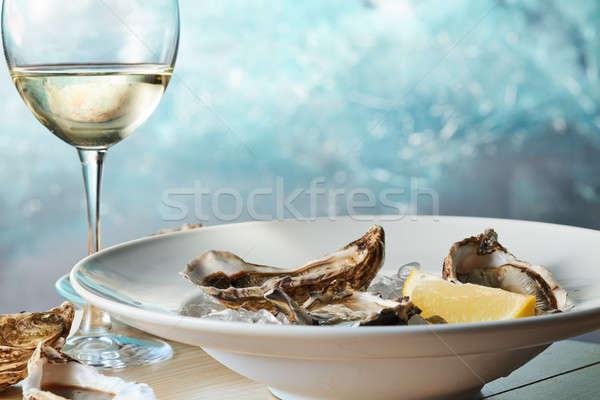 Fresh raw oysters on ice with lemon Stock photo © artjazz