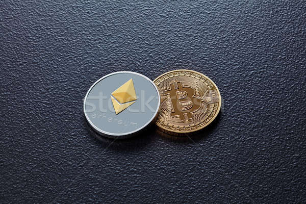 Two coins of crypto currency ETH, BTC on a black concrete background. Business, finance and technolo Stock photo © artjazz