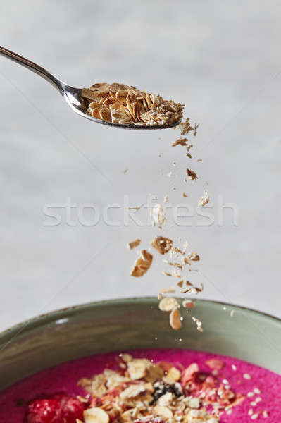 oat flakes in a spoon over a red smoothie in a pial on a concrete background Stock photo © artjazz