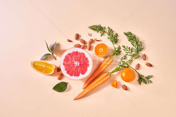 Carrot, slices of orange and grapefruit, mandarins, almonds, green leaf on a paper background. Conce Stock photo © artjazz