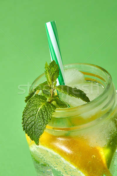A sprig of green mint in focus in a glass jar with a cold natural homemade lemonade isolated on gree Stock photo © artjazz