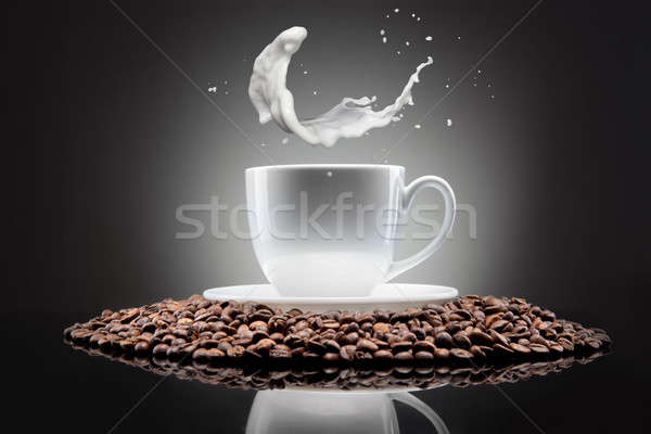 white cup with coffee beans and milk splash on black Stock photo © artjazz