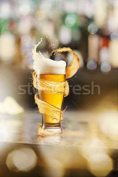 A cold glass of beer and a splash around on a blurred bar counter background Stock photo © artjazz